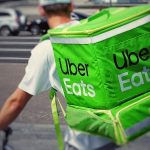 Food delivery worker wearing an Uber Eats backpack illustrating an article on keeping delivery tips