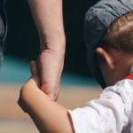 Photo of parent holding hands with little boy to illustrate article on child support payments from state to state